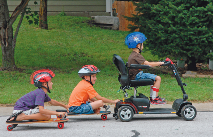 A picture of a little boy in a wheelchair, rolling down a hill with two other little boys on skateboards