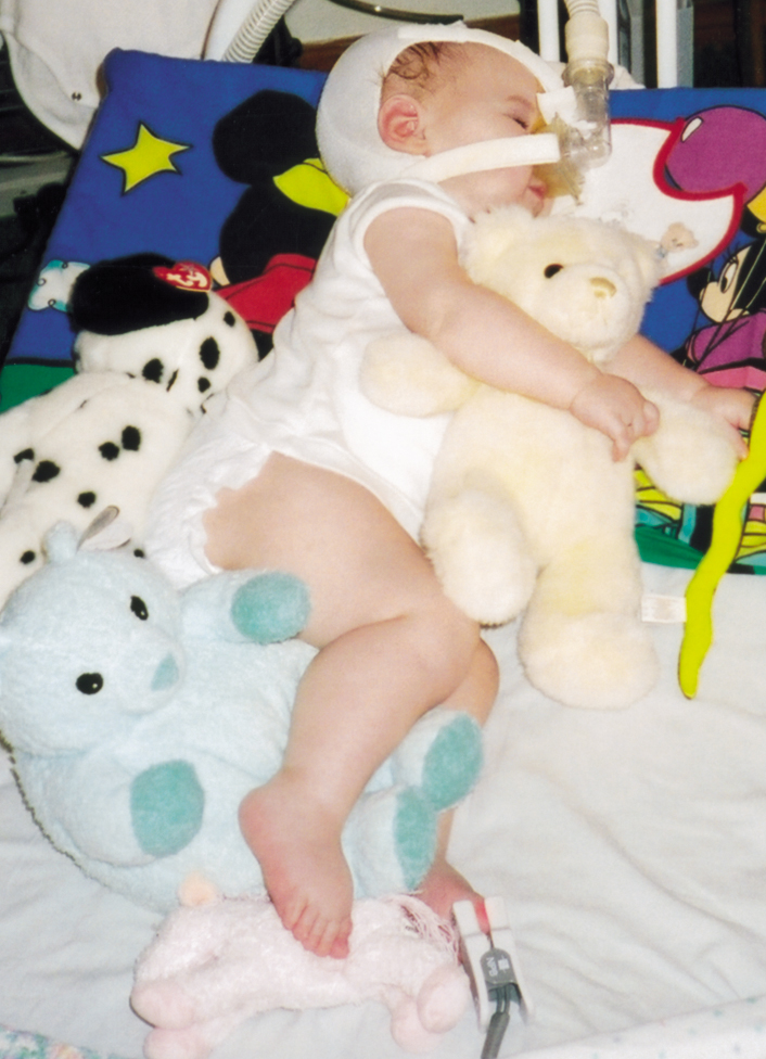Stuffed animals are used to adjust Adrianne's position frequently.