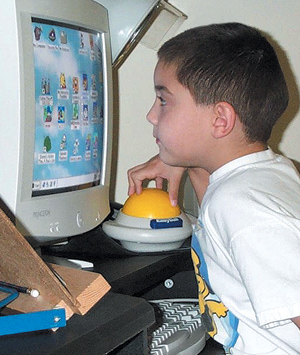 Boy using a specially adapted computer for his vision