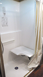 A roll-in shower with a fold-down seat allows wheelchair user, to transfer easily for a sit-down shower.