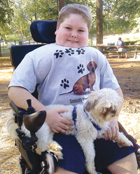 Jared Watson, prior to his spinal surgery, wearing a back brace and holding his dog, Gizmo.
