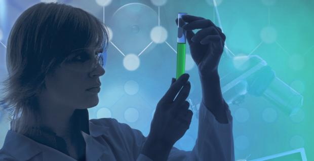 A picture of a scientist with a green vial
