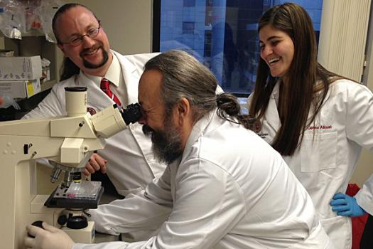 Noah Weisleder (left) in his laboratory working with Eric Beck (center) and Jenna Alloush (right) on a fluorescence microscope used to examine muscle cell viability in dystrophic mouse models.