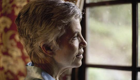An elderly woman staring out of a window