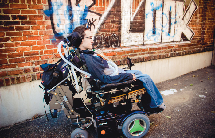 A picture of Jared Aronson. He sits in a wheelchair in front of a brick wall with grafitti on it