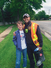 Grant (left) delivers water to a Wichita fire fighter during a Fill the Boot event.