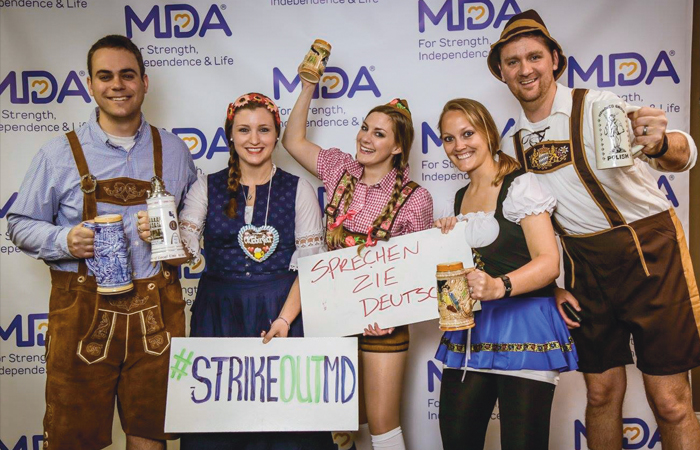 A group of happy people in traditional German clothing, supporting the MDA at an event