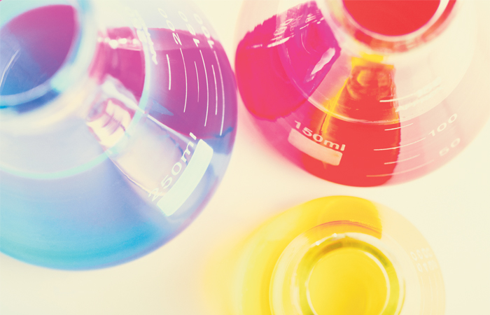 A bright and colorful picture of several beakers full of colored liquids