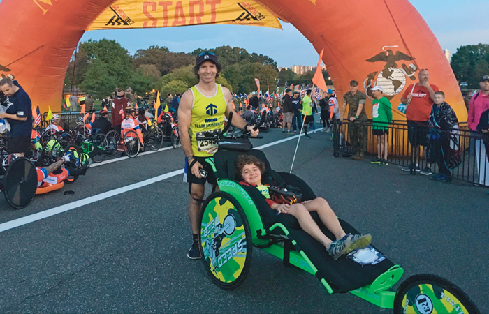 A picture of Will Farr, wearing a Team Momentum jersy, at the start line for the Washington D.C. Marine Corps Marathon