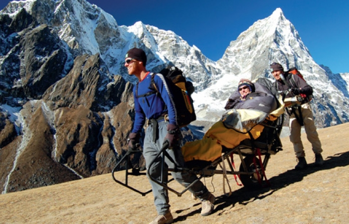A picture of three people climbing a mountain, one of them in a specially made mountain climbing wheel chair