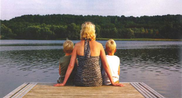 A picture of a woman sitting on a dock with two little boys